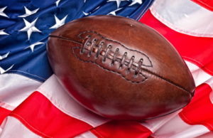 american football on top of a US flag