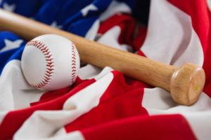 baseball bat on glove resting on a US flag