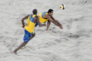 diving for the ball in a mens beach volleyball game