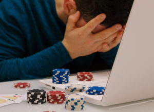 gambler sitting head in hands in front of laptop casino and poker chips on top