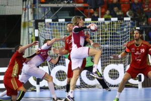 handball player being tackled and ready to shoot