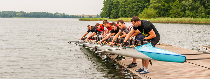 men lifting rowing boat into the water