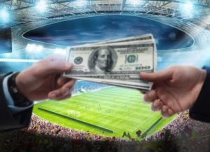 money changing hands with football stadium in background
