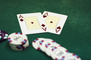 pair of aces and chips on green cloth casino table