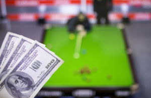 snooker match blurred with money in foreground