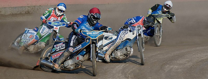 speedway riders drifting around a bend