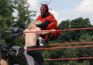 wrestler performs head hold in a costume